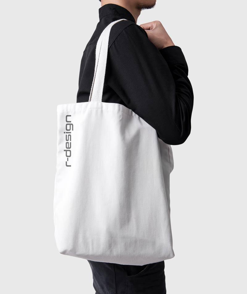 Mann mit dunkler Kleidung und weißer Baumwolltasche auf der Schulter. Werbetasche ist beschriftet mit Logo. Werbetaschenonline