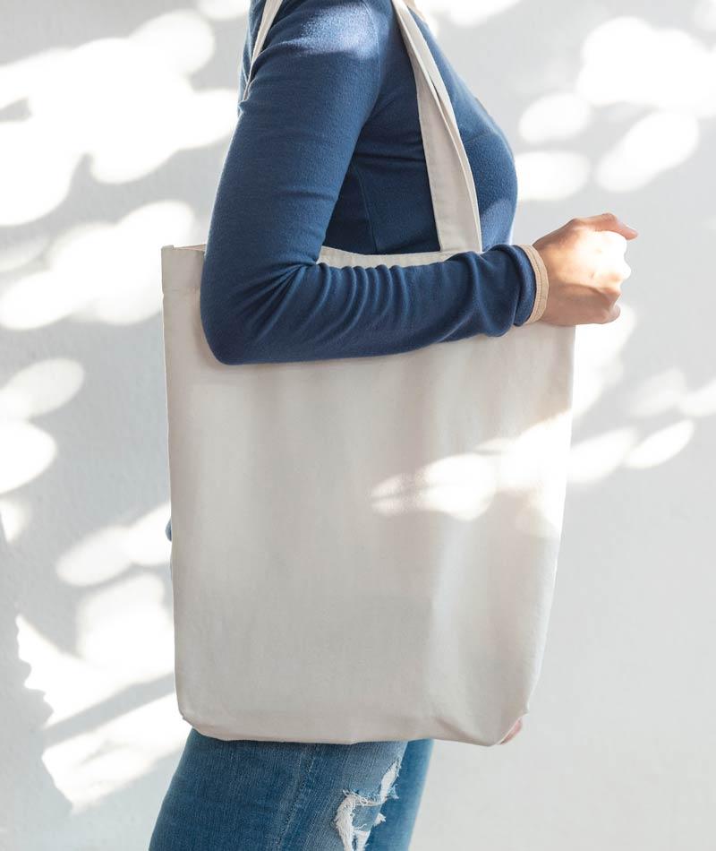 Frau trägt weiße naturbaumwolltasche / werbetasche auf der schulter.
