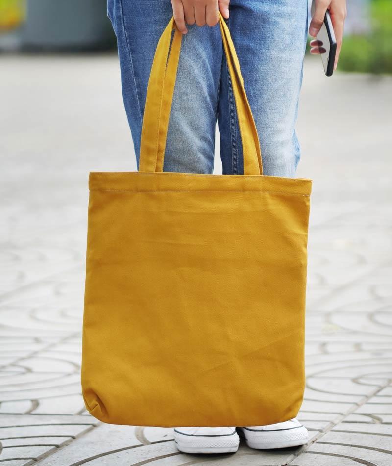 Frau hält gelbe Werbetasche in der Hand. Werbetaschenonline